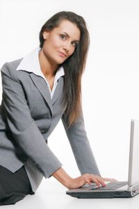 Businesswoman at laptop in grey